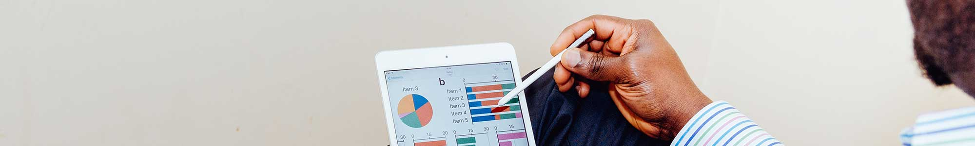 Afbeelding van een man die met een stylus op een tablet grafieken bekijkt en aanklikt