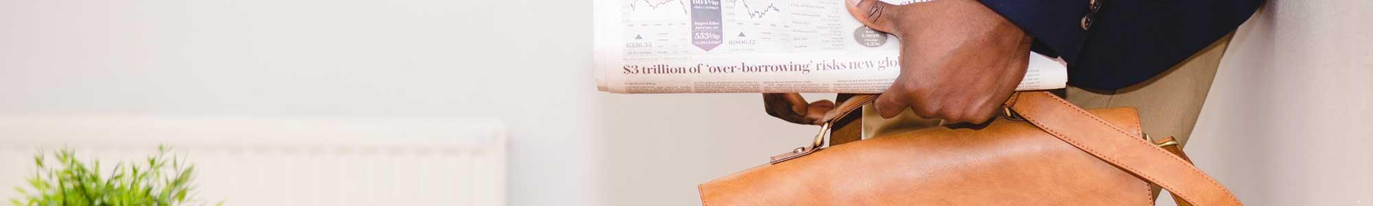 Afbeelding van man die een aktetas met krant vasthoudt