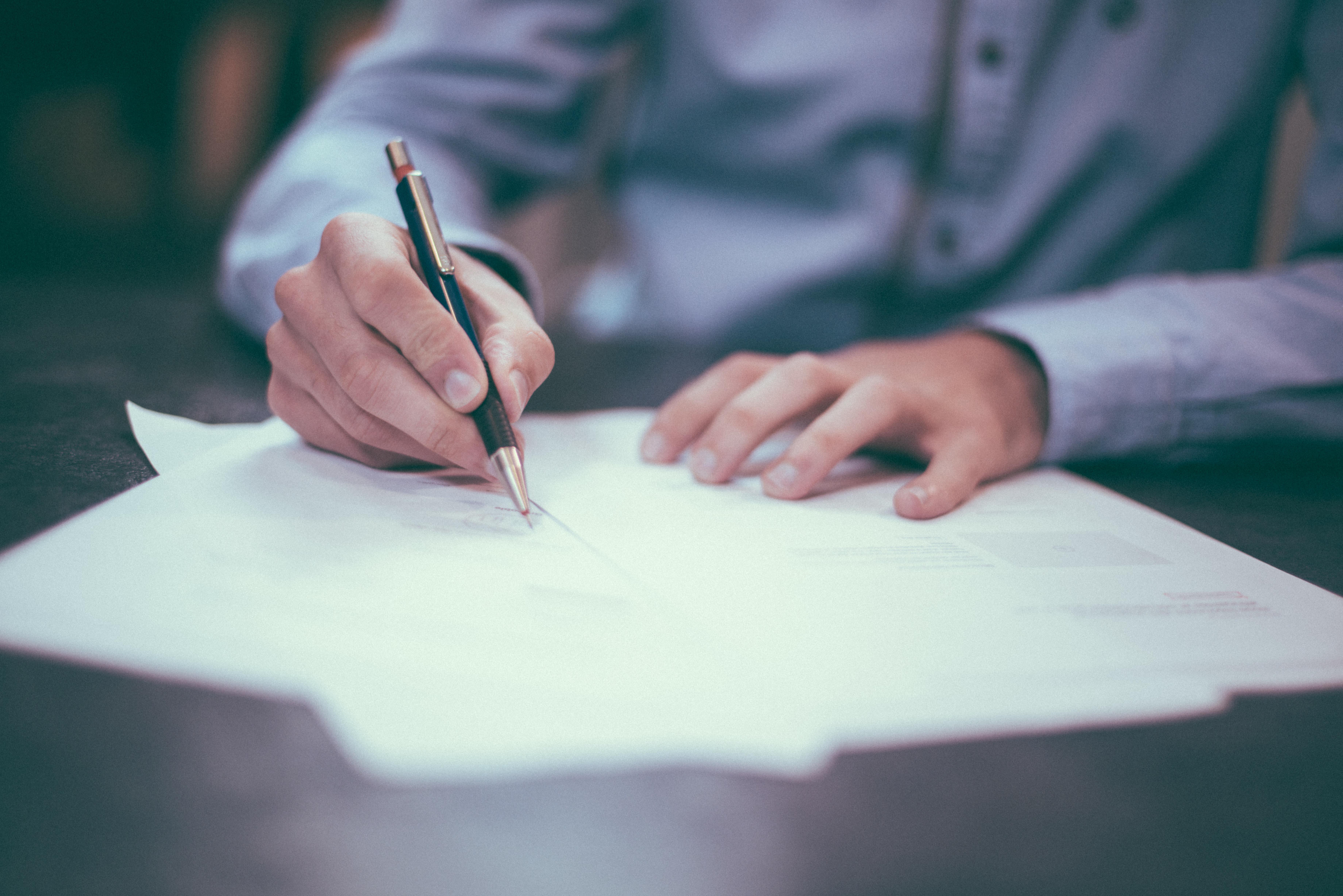 Afbeelding van een man die achter een bureau zit en die aantekeningen maakt op vellen papier