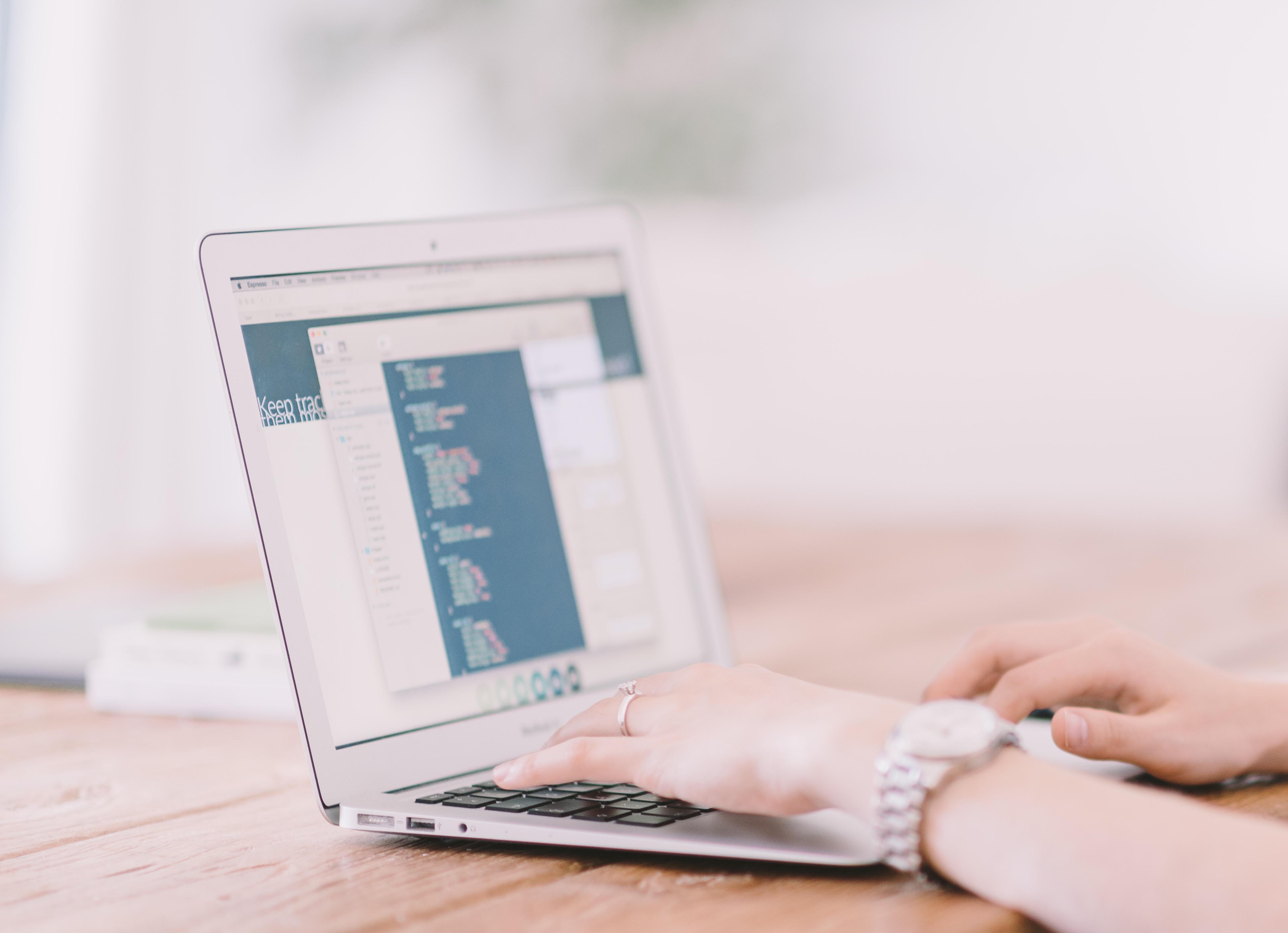 Afbeelding van de handen van een vrouw die achter een laptop code typt